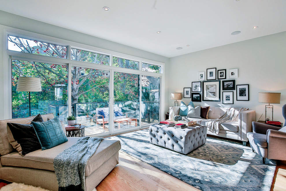 Inspiration for a mid-sized transitional open concept light wood floor living room remodel in Toronto with gray walls, a standard fireplace, a wood fireplace surround and no tv