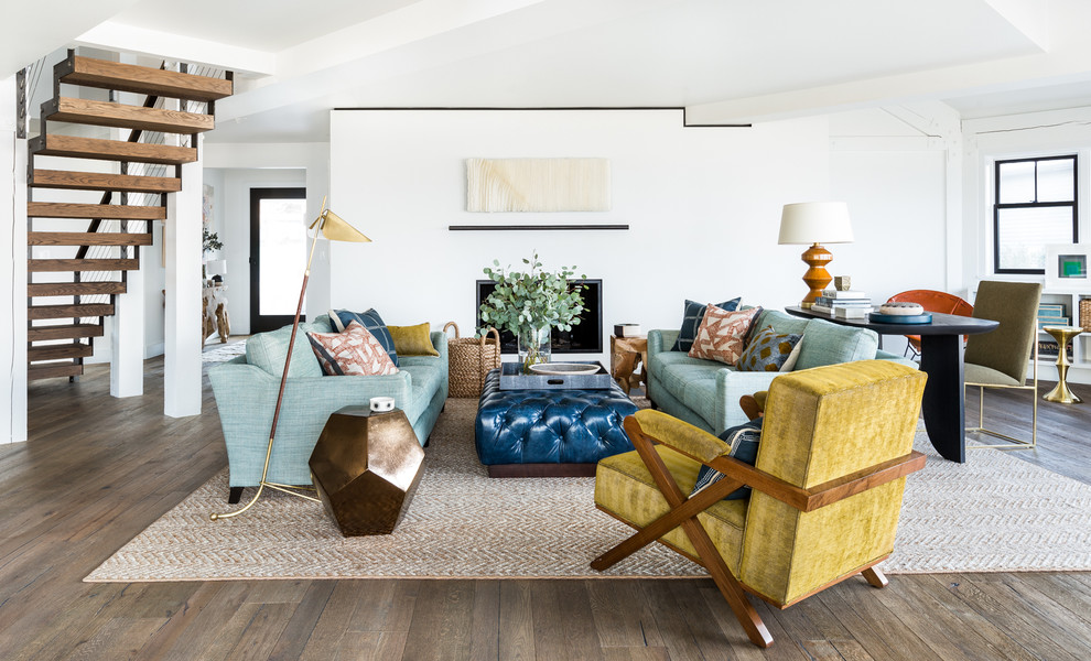 Example of a beach style open concept medium tone wood floor living room design in Seattle with white walls, a standard fireplace and a plaster fireplace
