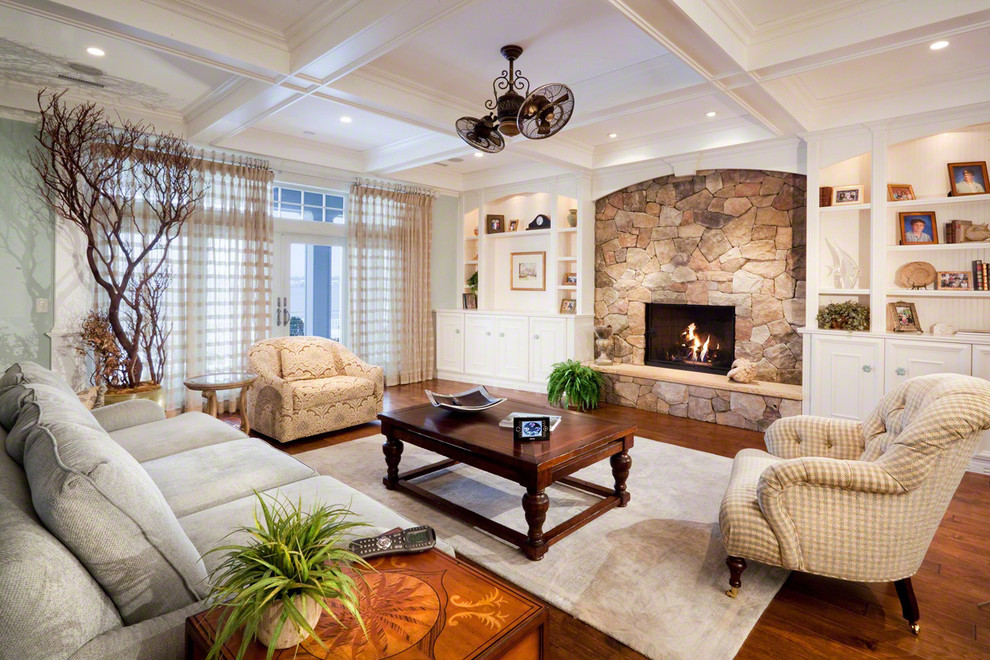 Living room - traditional medium tone wood floor living room idea in New York with green walls, a standard fireplace and a stone fireplace