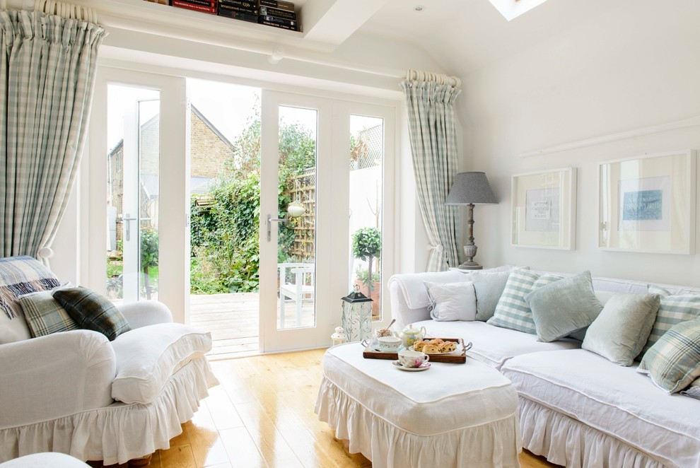 Inspiration for a small shabby-chic style medium tone wood floor living room remodel in Kent with white walls