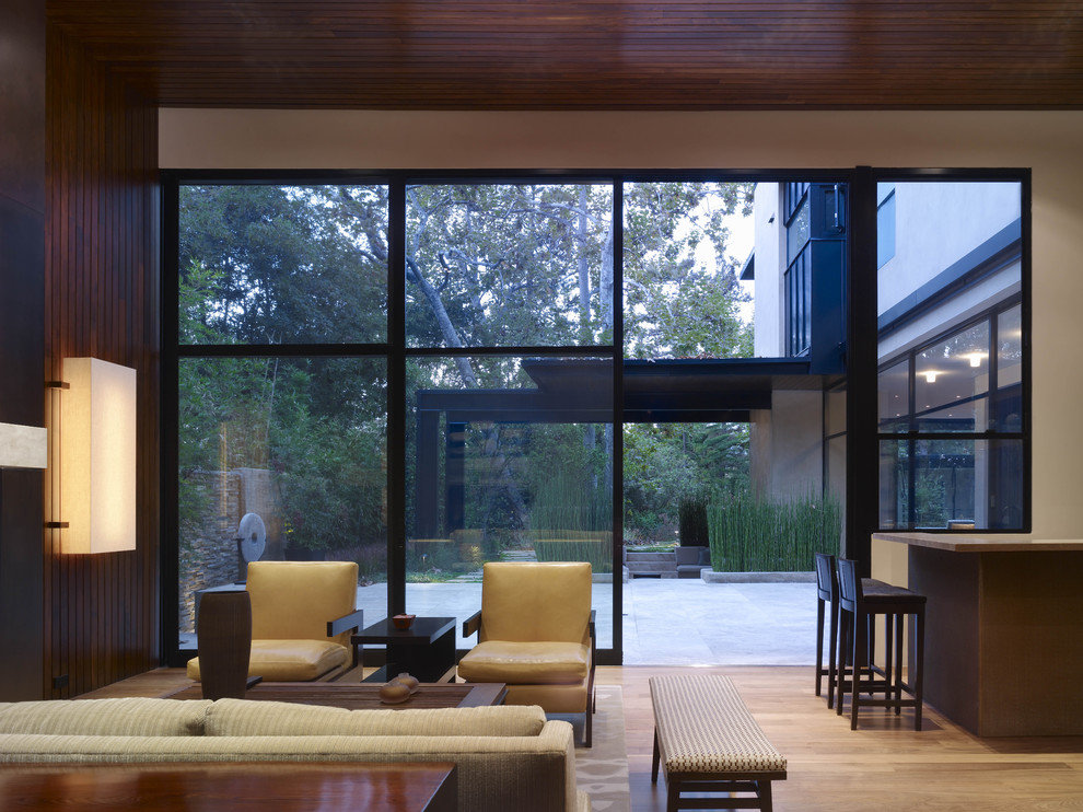 Living room - contemporary open concept light wood floor living room idea in Los Angeles with brown walls