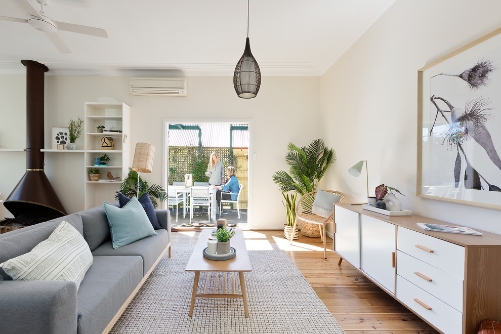 Mid-sized beach style open concept and formal medium tone wood floor and beige floor living room photo in Sydney with a wood stove and beige walls