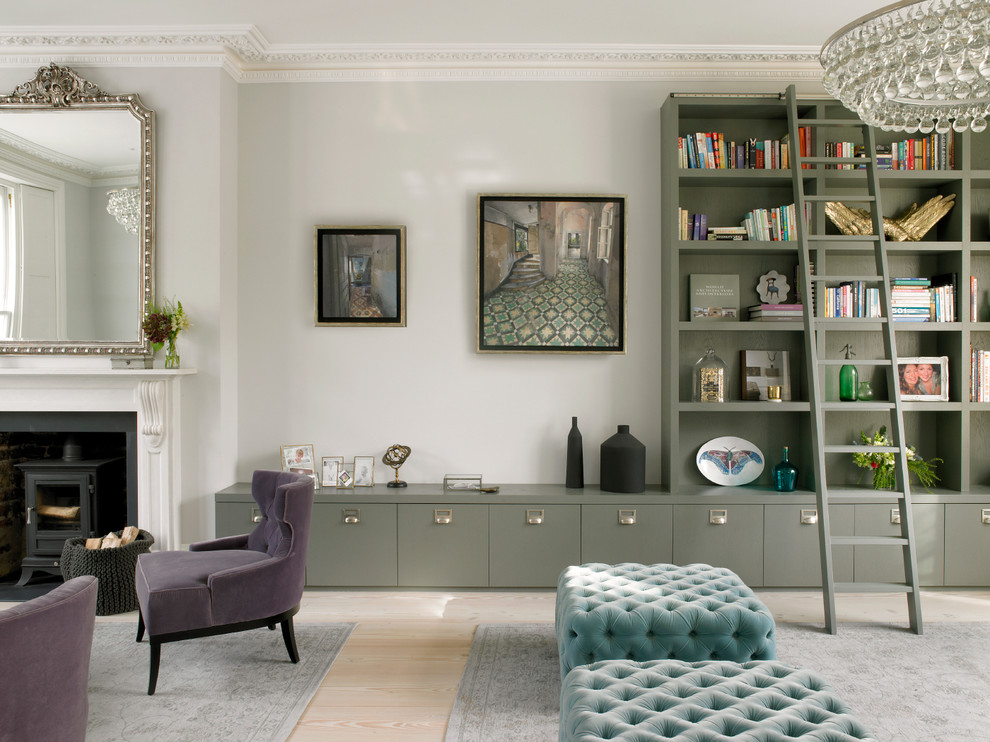 Example of a large transitional open concept light wood floor and beige floor living room design in London with gray walls, a standard fireplace, a stone fireplace and no tv