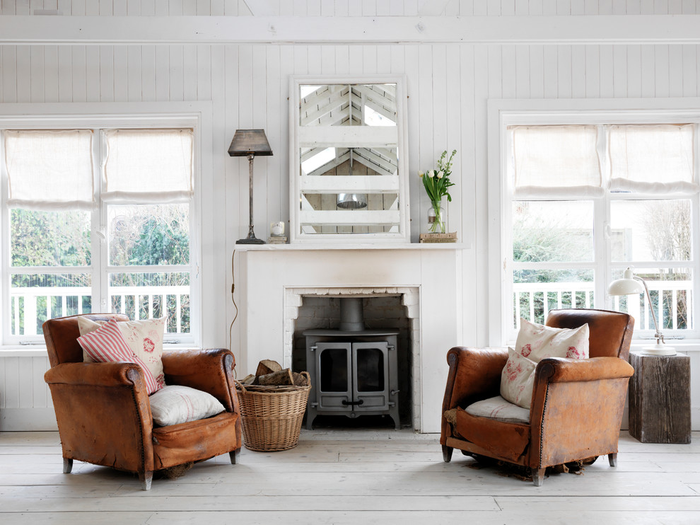 Design ideas for a romantic living room in London with white walls, light hardwood flooring and a wood burning stove.