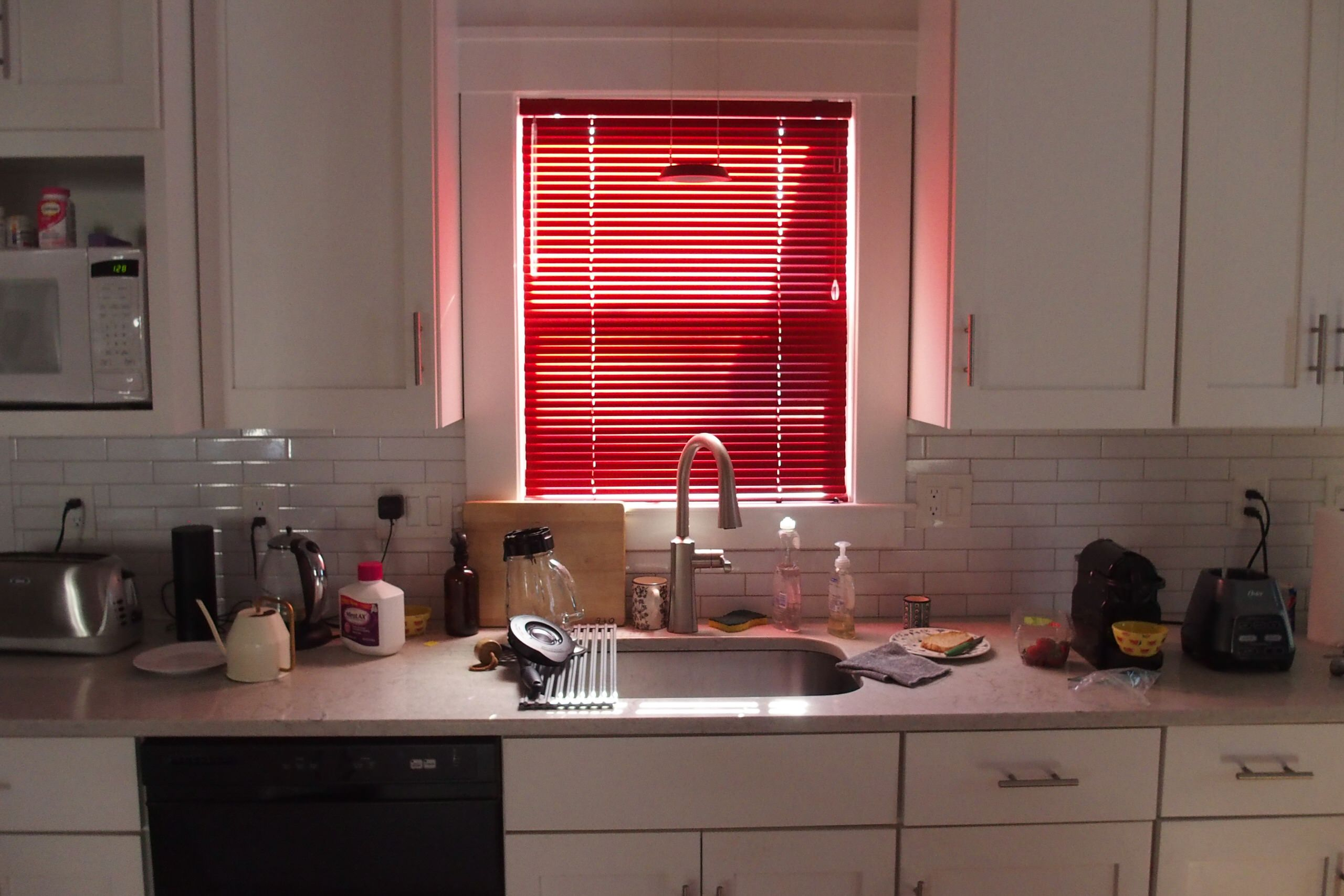 Window treatments in a white living room and kitchen
