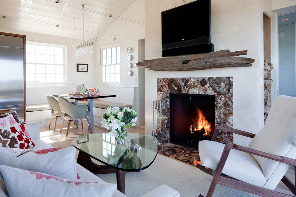 Example of a small coastal open concept light wood floor living room design in Boston with a standard fireplace, a wall-mounted tv, white walls and a stone fireplace
