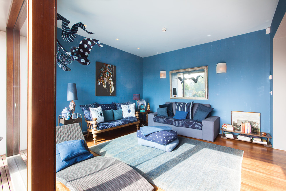 Design ideas for a medium sized bohemian open plan living room in London with blue walls and medium hardwood flooring.