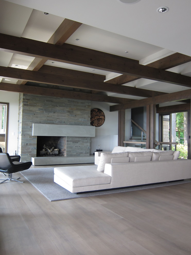 Large trendy formal and open concept light wood floor and beige floor living room photo in Vancouver with white walls, a standard fireplace and a stone fireplace