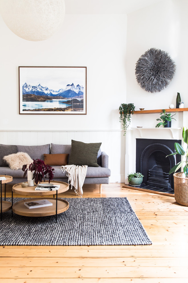 Example of a trendy open concept light wood floor and brown floor living room design in Melbourne with white walls, a standard fireplace, a metal fireplace and a tv stand