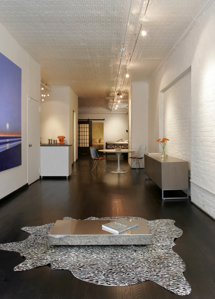 Example of an urban dark wood floor living room design in New York with white walls