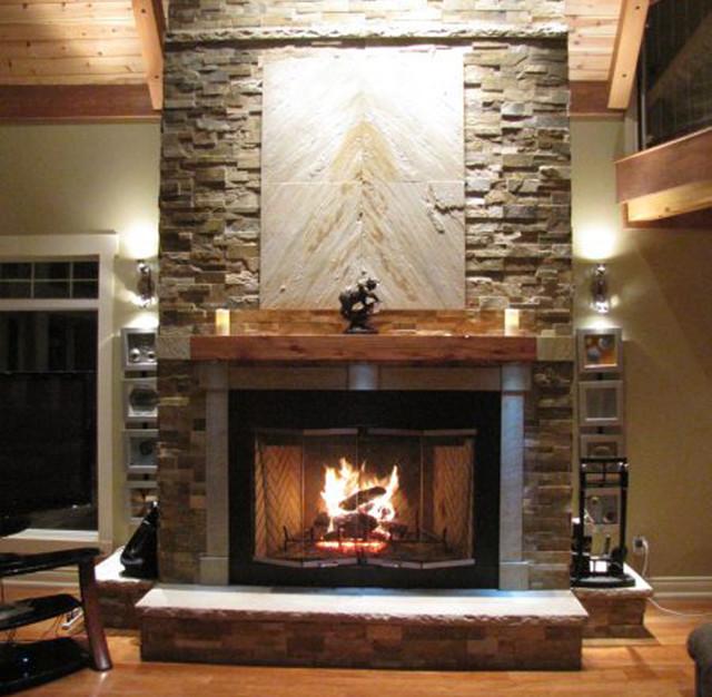 Asian inspired stacked stone fireplace with wood mantel and exposed beams.