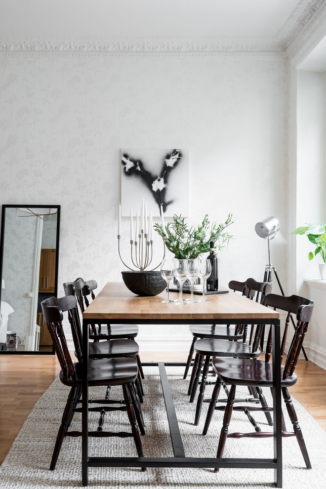 Mid-sized danish medium tone wood floor and brown floor kitchen/dining room combo photo in Gothenburg with white walls