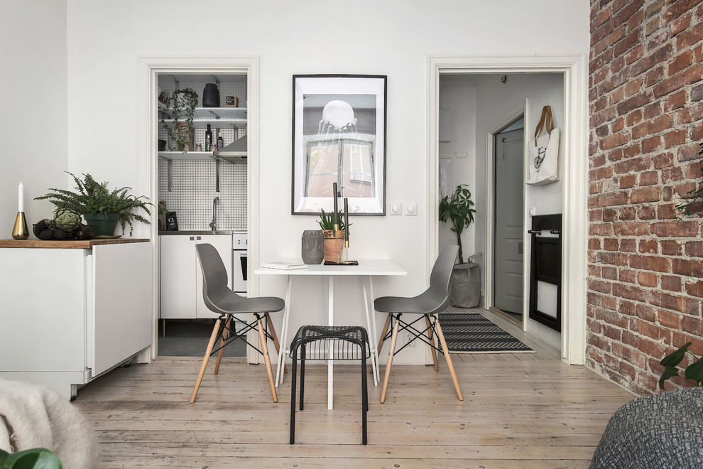 Example of a small danish light wood floor dining room design in Stockholm with white walls