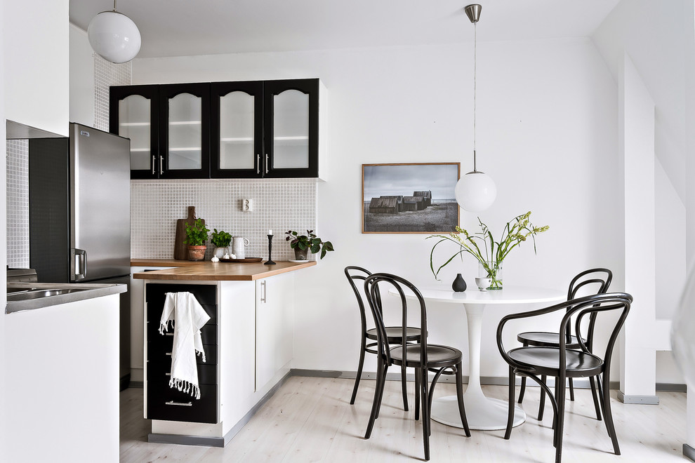 Example of a small danish light wood floor and beige floor kitchen/dining room combo design in Gothenburg with white walls
