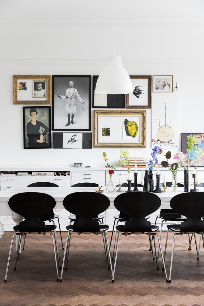 Example of a mid-sized danish medium tone wood floor dining room design in Malmo with white walls and no fireplace