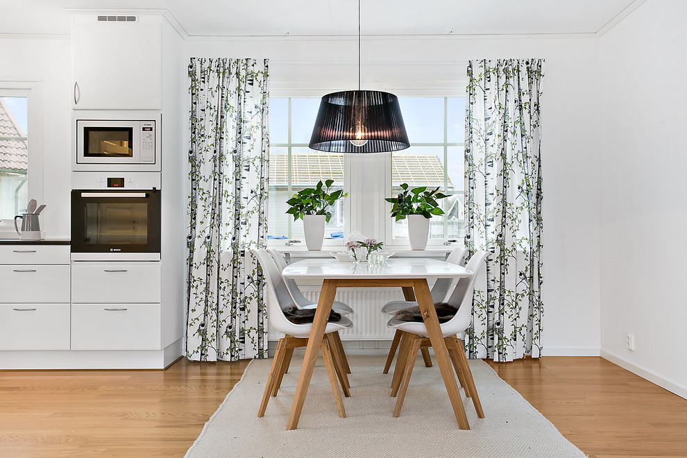 Mid-sized danish medium tone wood floor kitchen/dining room combo photo in Other with white walls and no fireplace