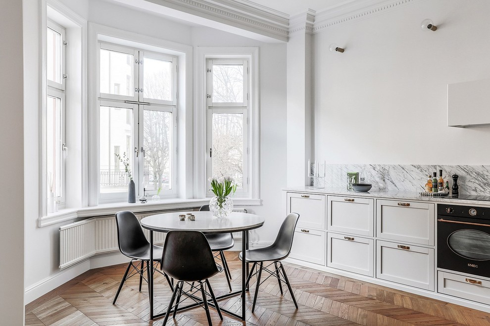 Kitchen/dining room combo - large scandinavian medium tone wood floor and brown floor kitchen/dining room combo idea in Malmo with white walls