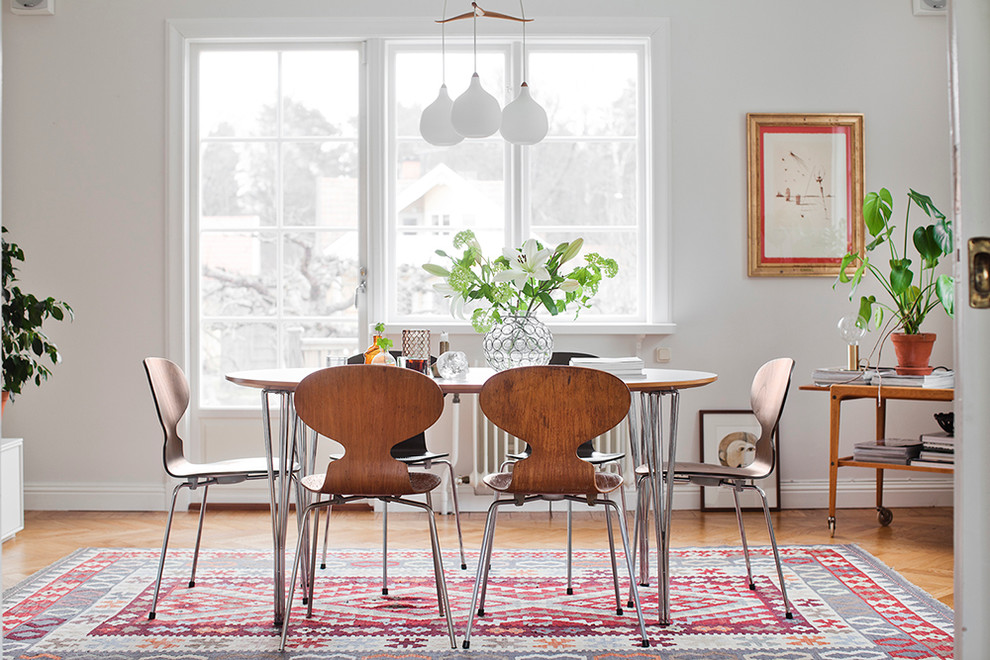 Inspiration for a mid-sized scandinavian medium tone wood floor dining room remodel in Stockholm with white walls