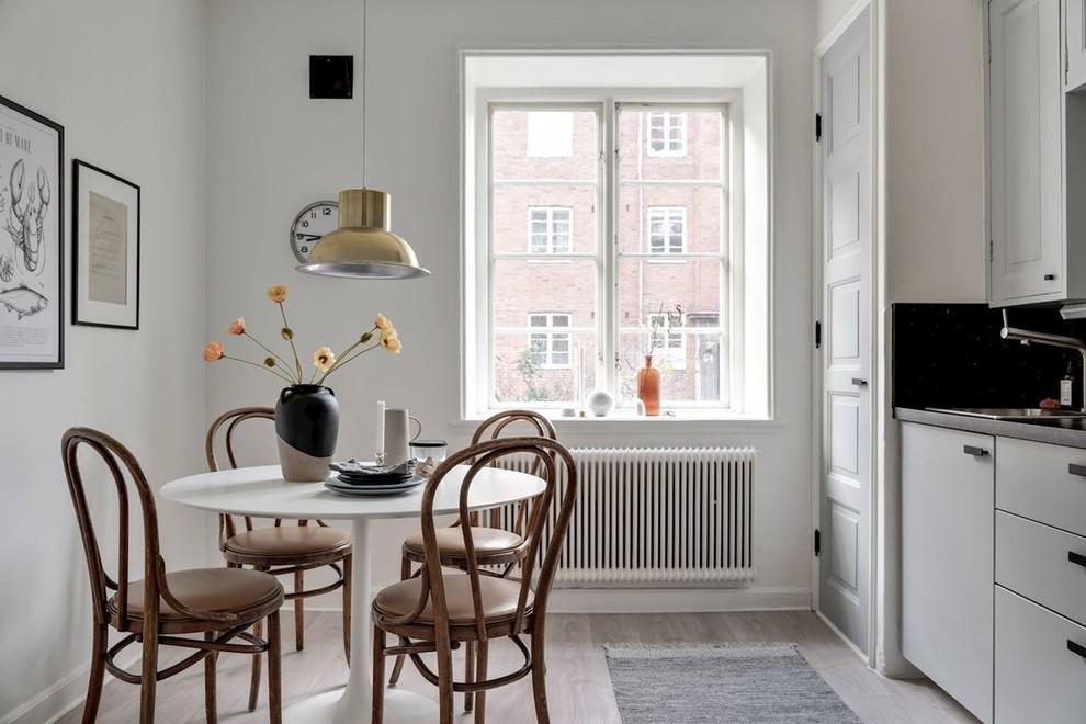Exempel på ett minimalistiskt kök med matplats, med vita väggar, ljust trägolv och grått golv