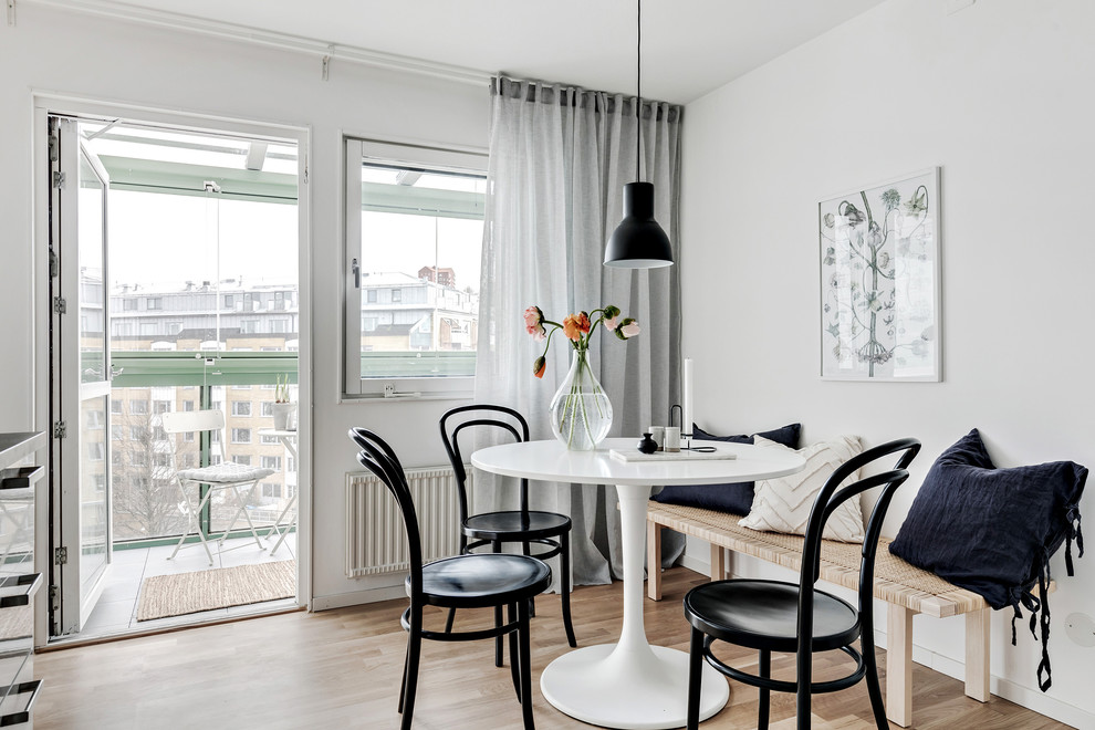 Example of a small danish beige floor and light wood floor dining room design in Gothenburg with white walls