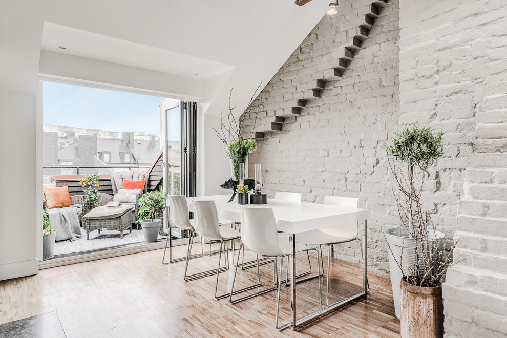 Example of a mid-sized danish light wood floor and brown floor great room design in Stockholm with no fireplace and gray walls