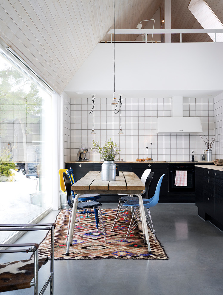 Example of a mid-sized danish concrete floor kitchen/dining room combo design in Stockholm with white walls and no fireplace