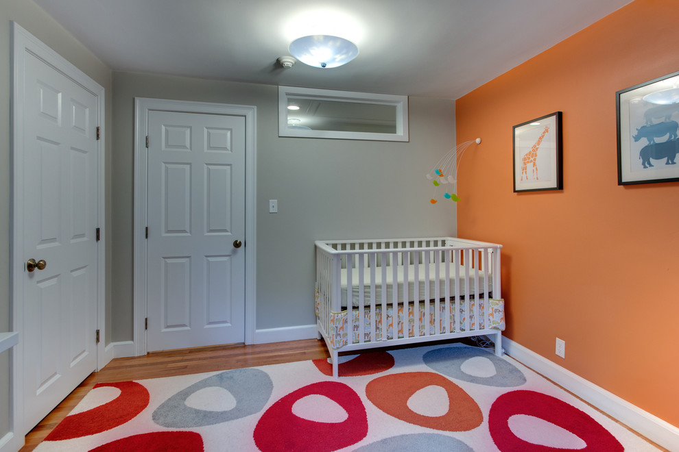 Example of a transitional gender-neutral medium tone wood floor nursery design in Boston with orange walls