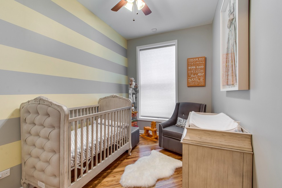 Inspiration for a small transitional gender-neutral medium tone wood floor nursery remodel in Chicago with gray walls