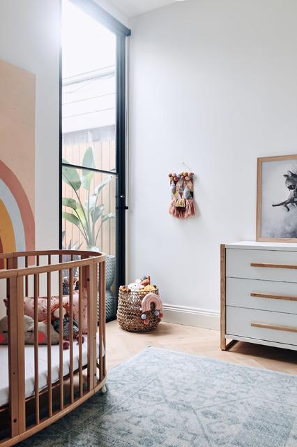 Esempio di una cameretta per neonati contemporanea con pareti bianche, parquet chiaro e pavimento beige