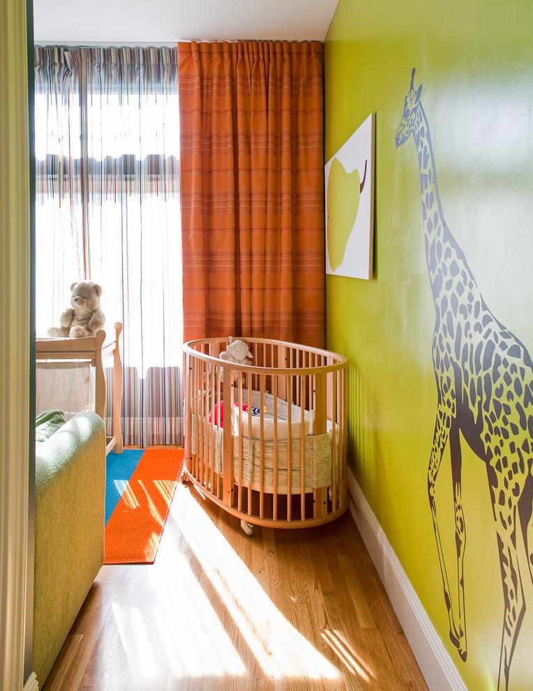 Esempio di una cameretta per neonati neutra design con pareti verdi e pavimento in legno massello medio