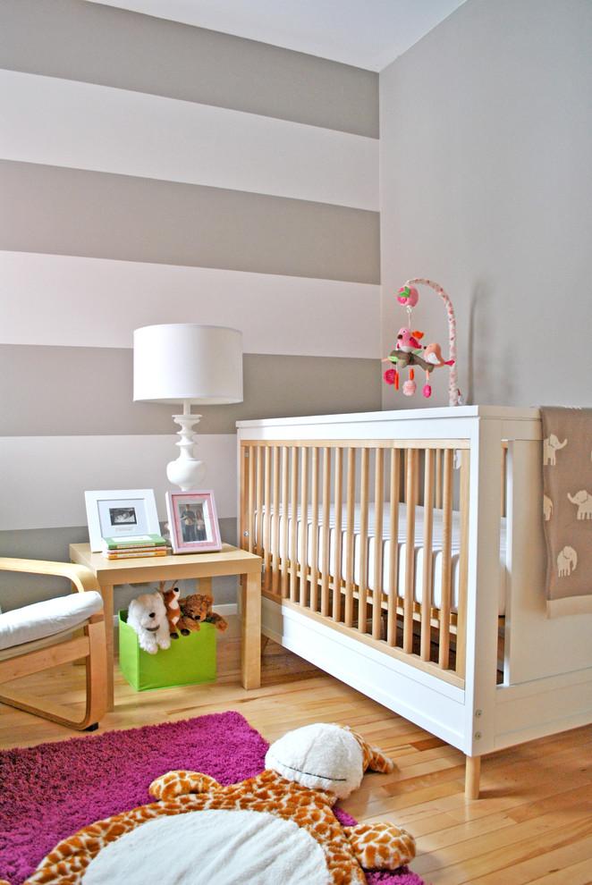 Nursery - contemporary gender-neutral medium tone wood floor nursery idea in Ottawa with gray walls
