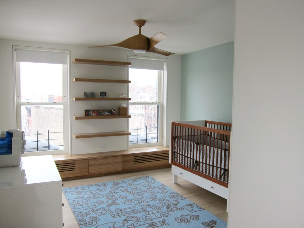 Mid-sized trendy gender-neutral light wood floor nursery photo in New York with blue walls