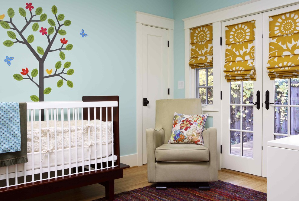 Inspiration for a mid-sized eclectic gender-neutral light wood floor and brown floor nursery remodel in San Francisco with blue walls