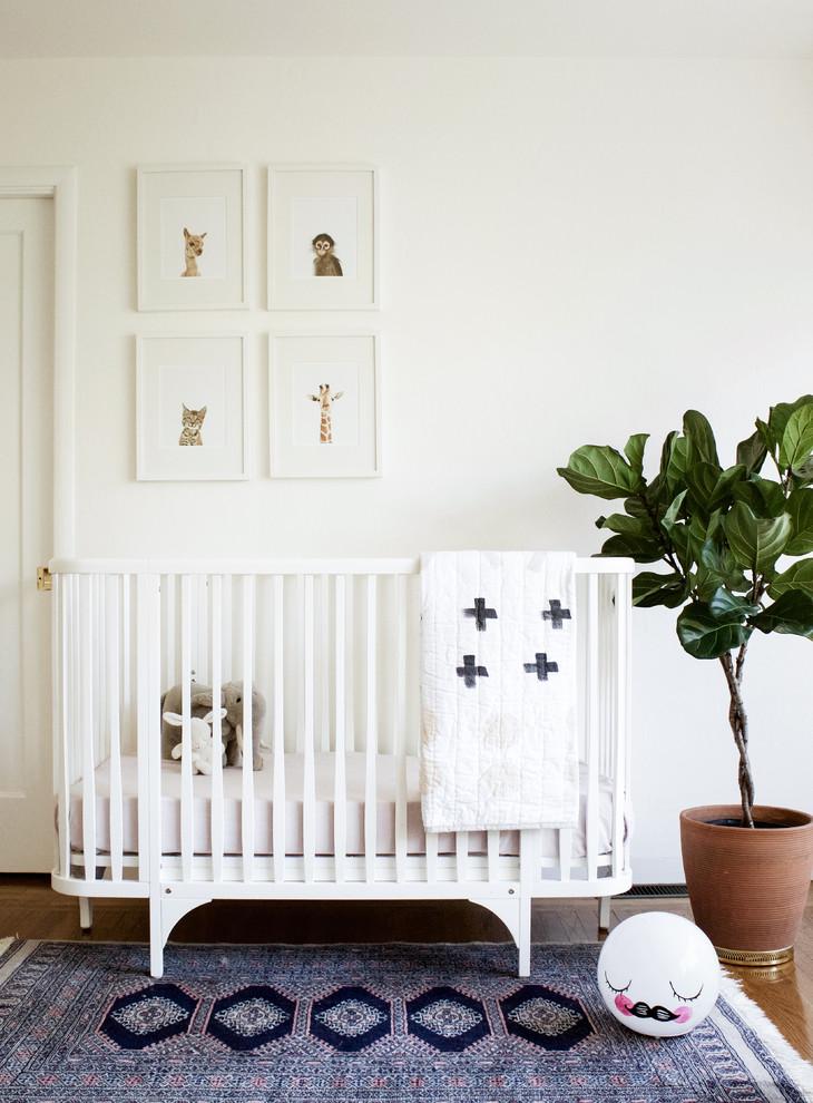 Nursery - scandinavian gender-neutral medium tone wood floor nursery idea in San Francisco with white walls