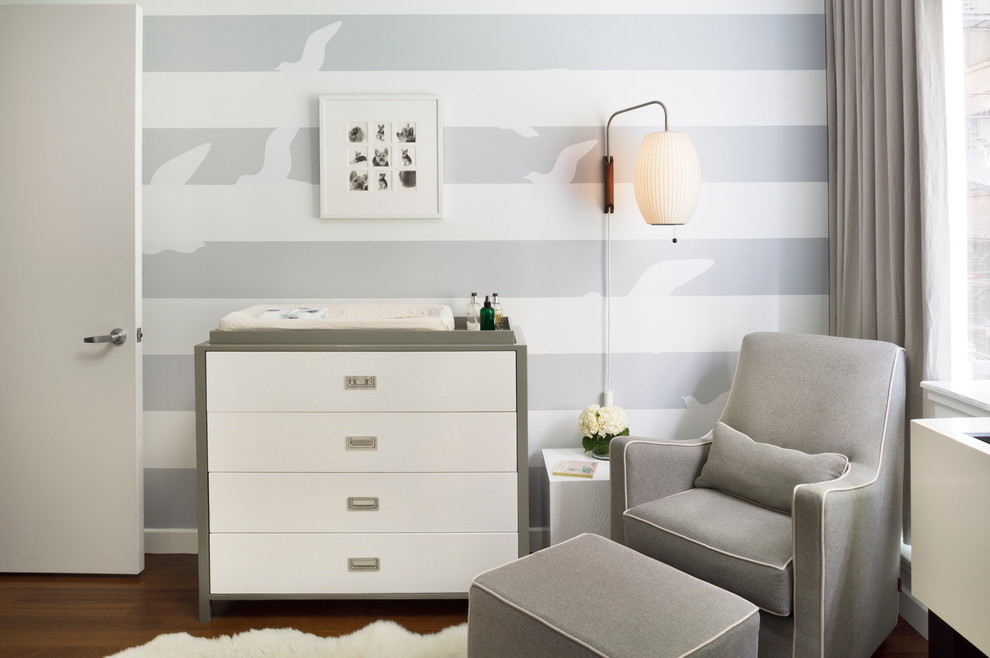 Example of a trendy gender-neutral dark wood floor nursery design in New York with gray walls