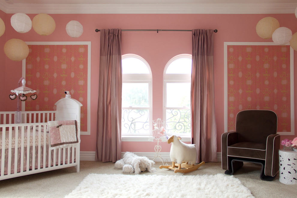 Example of a classic girl carpeted nursery design in Los Angeles with pink walls