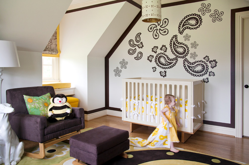 Inspiration for a large timeless girl medium tone wood floor nursery remodel in Little Rock with multicolored walls
