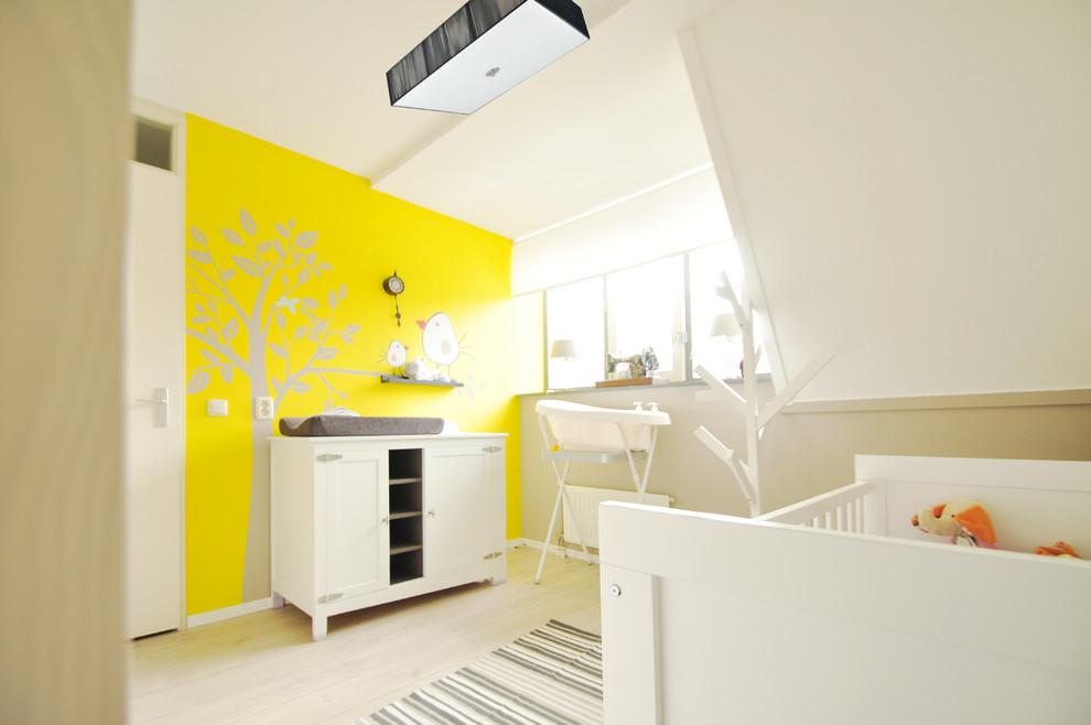 Nursery - contemporary gender-neutral light wood floor and beige floor nursery idea in Amsterdam with yellow walls