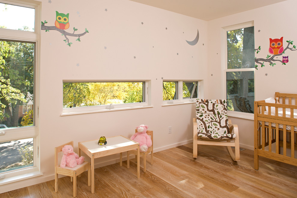 Inspiration for a contemporary gender-neutral light wood floor nursery remodel in Minneapolis with white walls