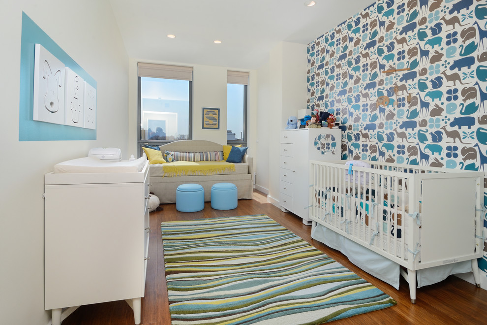 Mid-sized trendy boy medium tone wood floor nursery photo in New York with multicolored walls