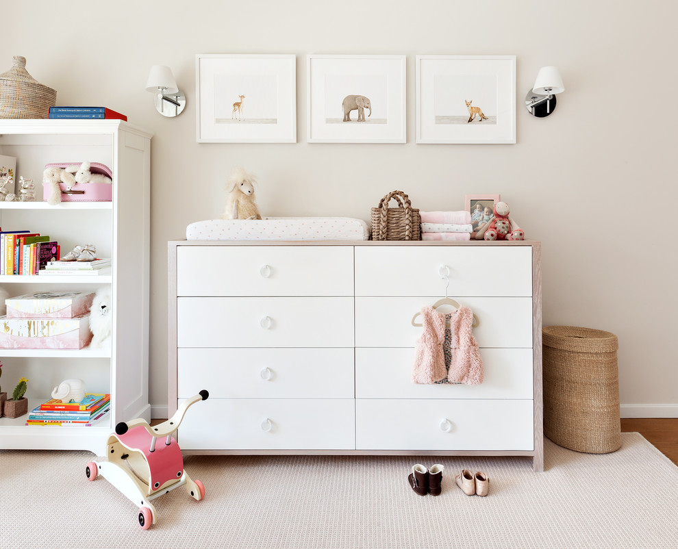 Inspiration for a mid-sized transitional girl medium tone wood floor nursery remodel in New York with beige walls