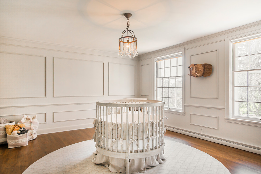 Example of a mid-sized transitional gender-neutral medium tone wood floor nursery design in Other with beige walls
