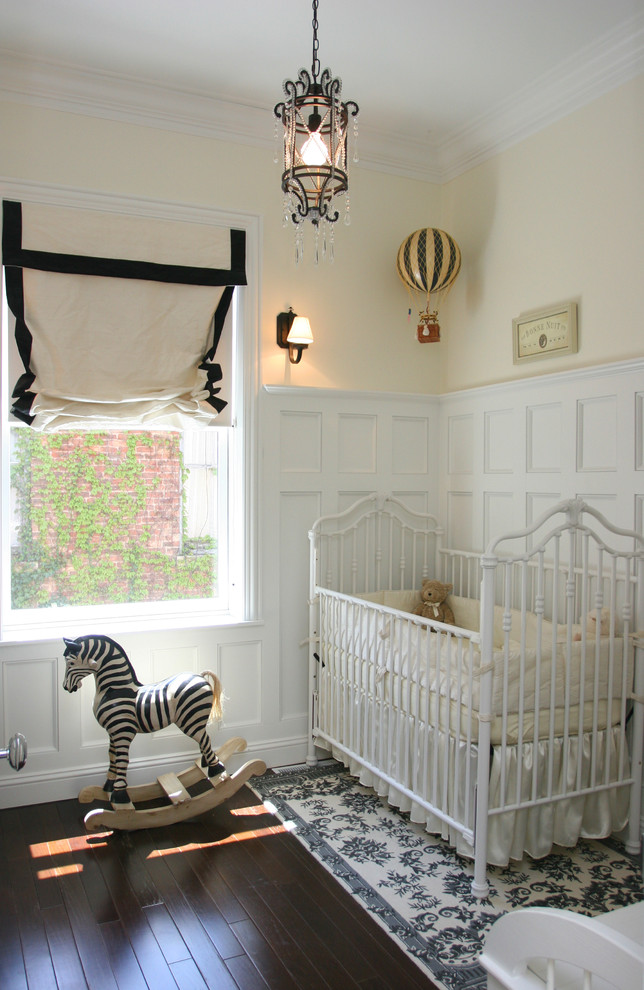 Inspiration for a mid-sized timeless gender-neutral dark wood floor nursery remodel in Chicago with yellow walls
