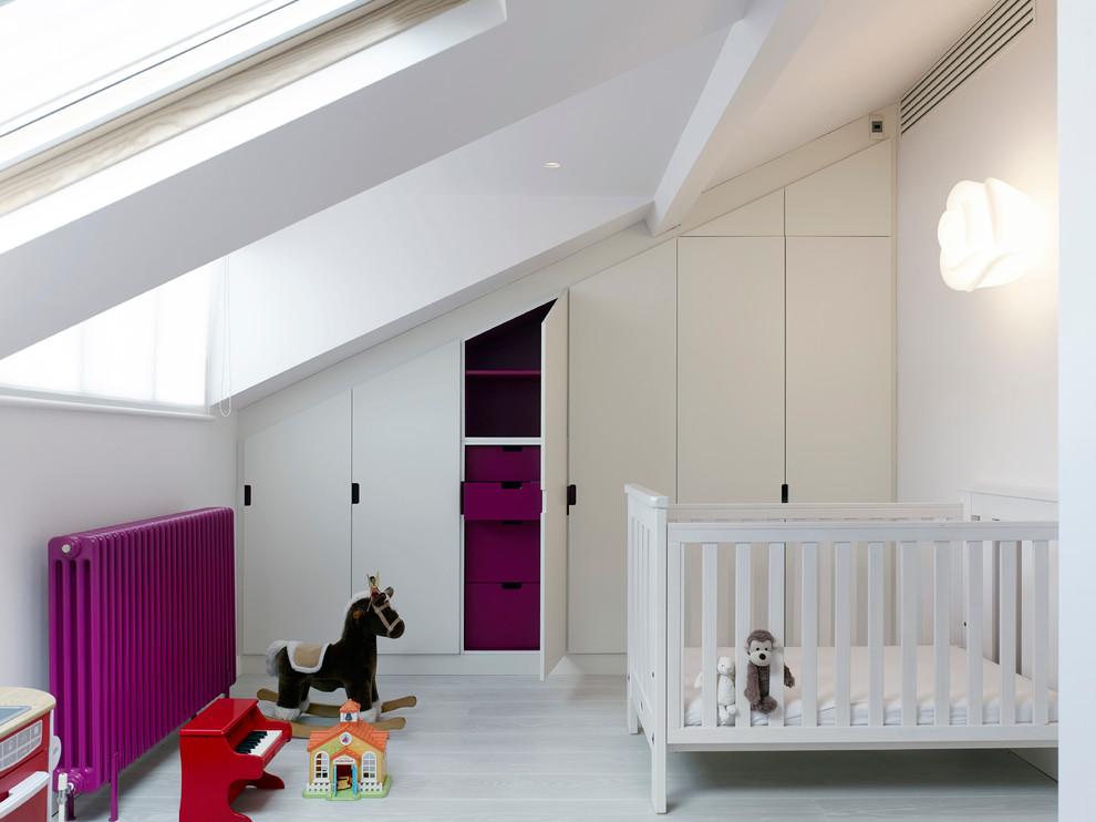 Gender-neutral painted wood floor nursery photo in London with white walls