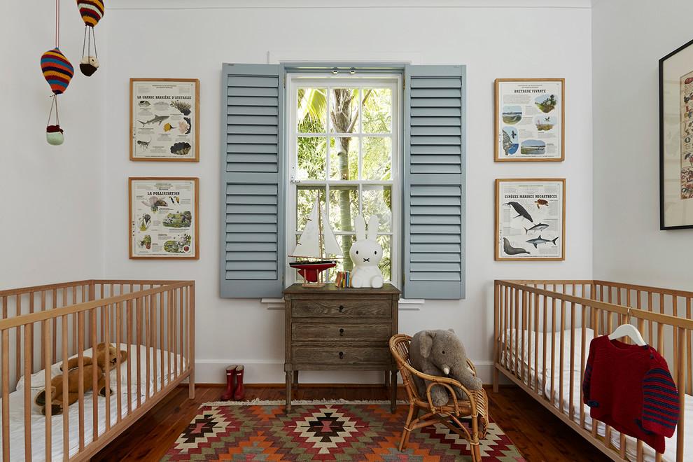 Elegant gender-neutral medium tone wood floor nursery photo in London with white walls