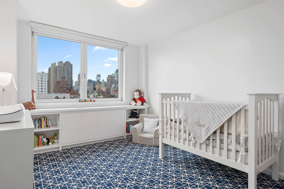 Example of a mid-sized transitional boy carpeted and blue floor nursery design in New York with white walls