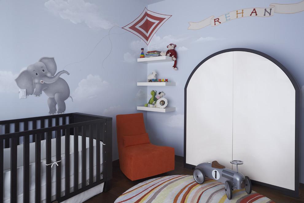 Trendy gender-neutral dark wood floor nursery photo in New York with blue walls