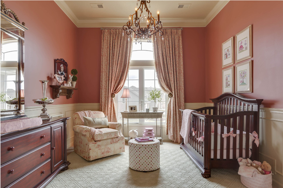 Inspiration for a mid-sized timeless girl nursery remodel in Kansas City with pink walls