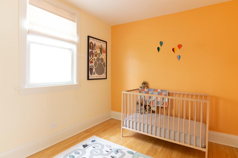 Danish gender-neutral light wood floor and yellow floor nursery photo in Chicago with orange walls