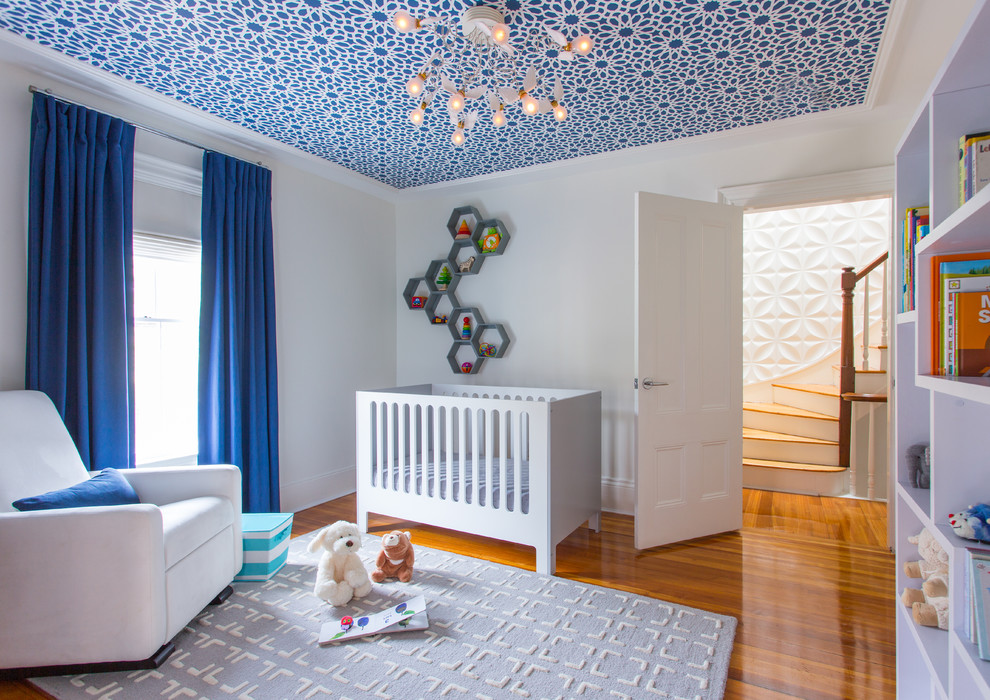 Nursery - mid-sized contemporary boy medium tone wood floor and orange floor nursery idea in Boston with white walls